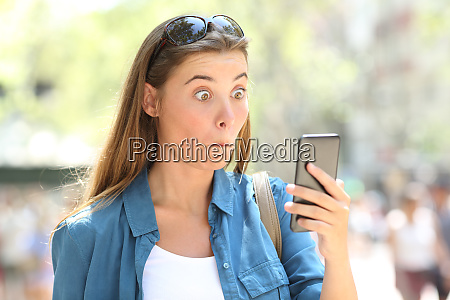 astonished woman reading phone content in