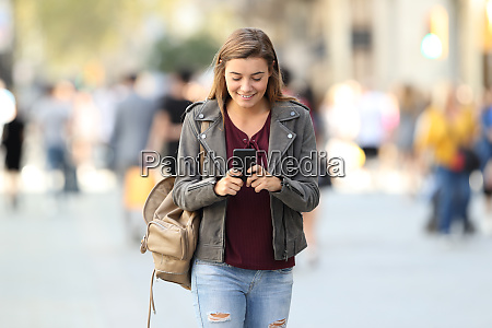 fashion girl walking texting on a
