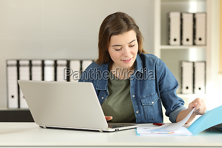 intern working comparing documents online at