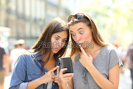 perplexed girls checking smart phone outdoors