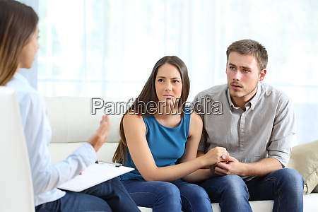 worried couple listening to marriage counselor