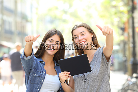 happy friends holding a tablet with