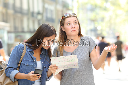 lost tourists consulting map and phone