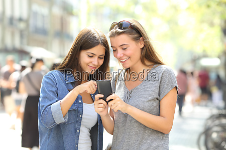 friends checking smart phone content in