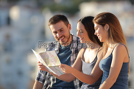 three tourists checking map in a
