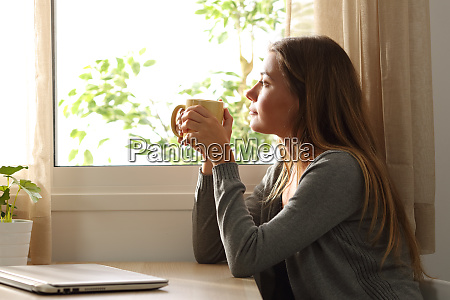 relaxed woman looking through a window