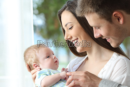proud, parents, playing, with, their, baby - 26548534