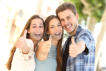 three happy friends smiling with thumbs