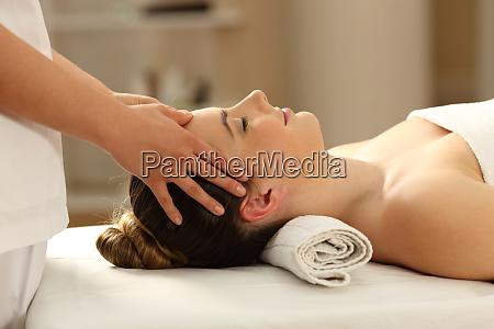 woman relaxing receiving a facial massage