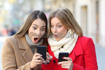 two amazed women finding content on