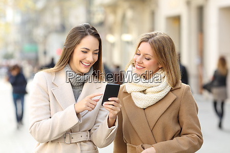 friends watching phone content in winter
