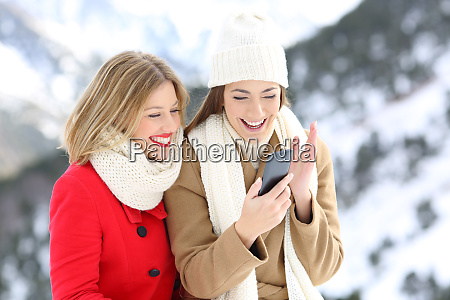 friends watching phone content on winter