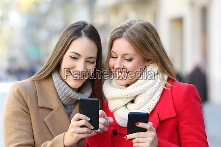 friends consulting smart phone in the