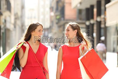 happy shoppers talking walking in the