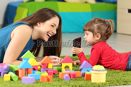 toddler showing phone to her mother