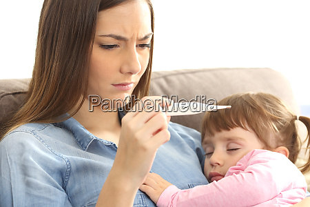 mother checking thermometer with her ill