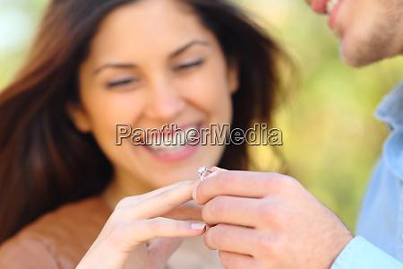 man putting engagement ring to his