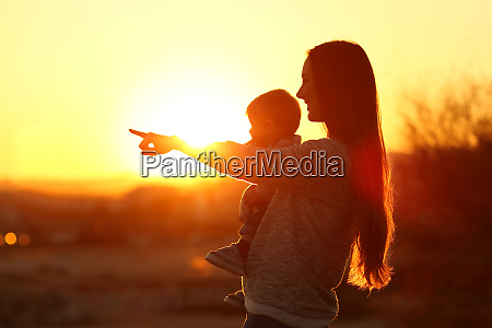 silhouette of a mother pointing horizon
