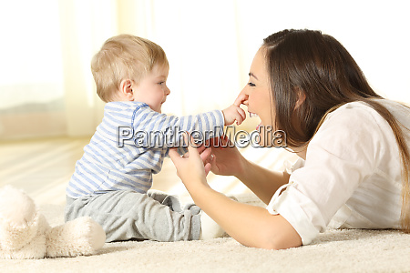 happy baby touching his mother face