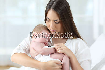 mother using a thermometer with her