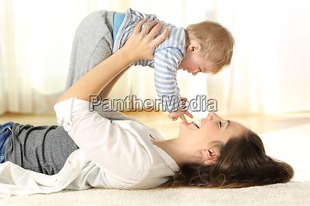 happy mother on the floor raising