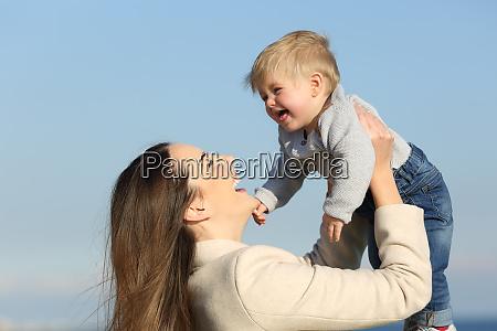 joyful mother playing raising her baby