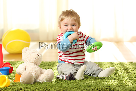 baby biting toys on a carpet