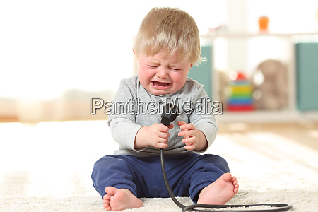 baby crying holding an an electric