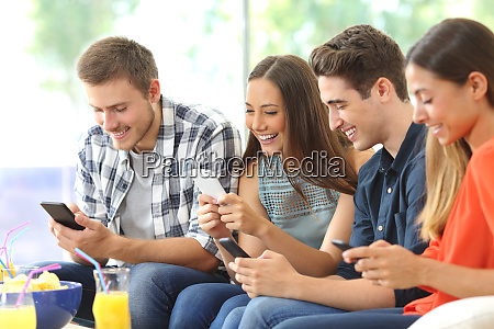 happy friends using their mobile phones