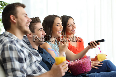 happy friends watching tv at home