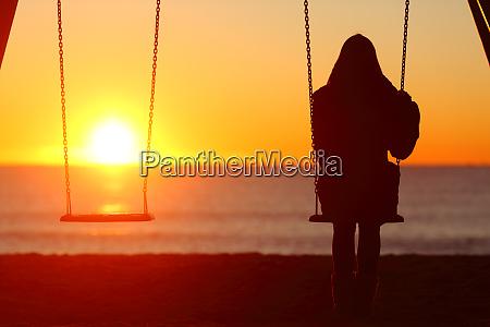 single woman sitting on a swing