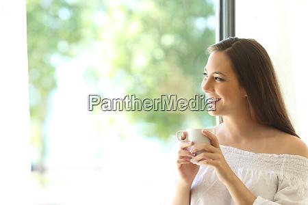 happy girl looking through window tasting