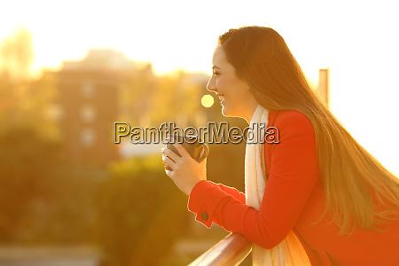 happy woman in a balcony looks