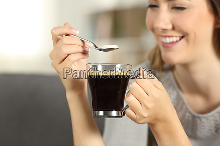 happy woman throwing sugar into coffee