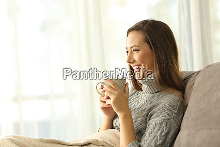 pensive woman holding a coffee mug