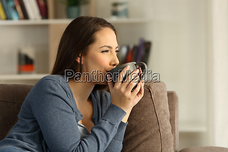 relaxed happy woman drinking coffee at