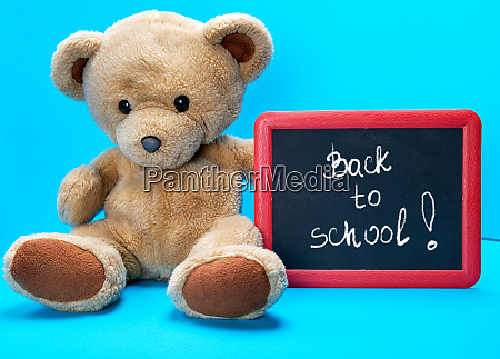 teddy bear holds red frame with