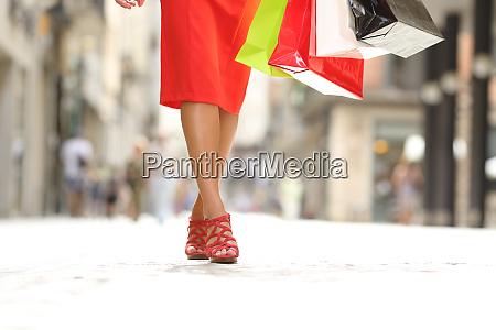 beauty woman legs walking holding shopping