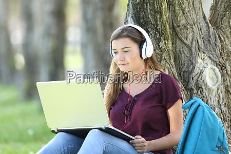 teen girl studying watching video tutorials
