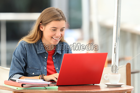 happy student typing on a laptop