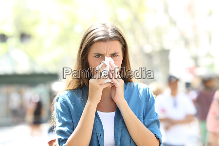 ill woman blowing mucus looking at