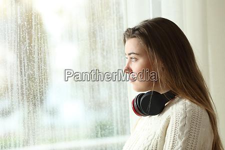 sad teen with headphones looking through