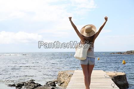 single tourist raising arms on summer