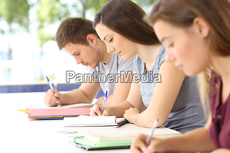 three students taking notes during a