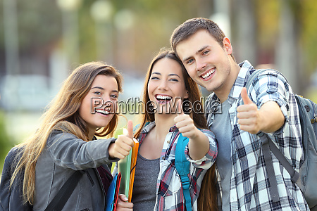 three happy students with thumbs up