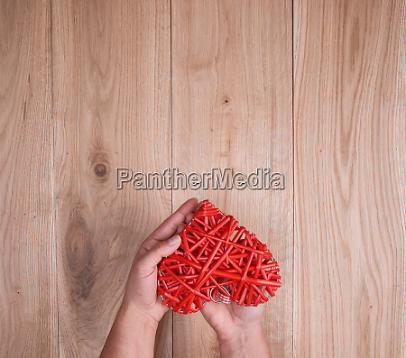 red heart in human hand on