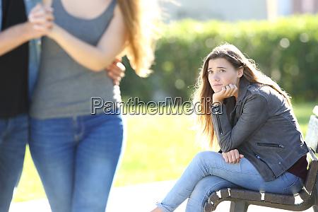 sad girl looking at a couple