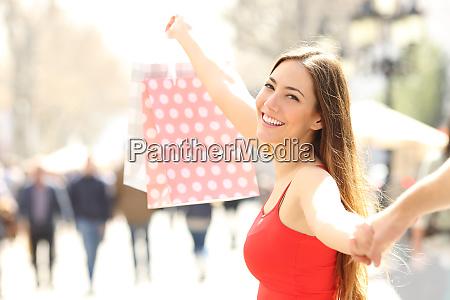 happy shopper walking showing shopping bag