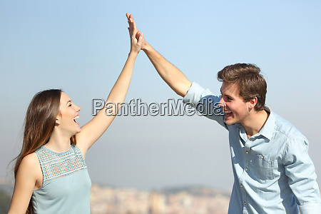 happy couple celebrating success giving five