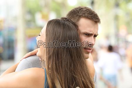 discontent boyfriend hugging his partner